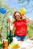 Eine Frau, die im roten Kleid und in den großen lustigen Sonnenbrillen auf Garten-PA aufwirft lizenzfreie stockbilder