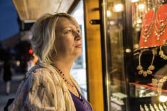 Eine Frau, die im Schmuckschaukasten schaut Stockbild