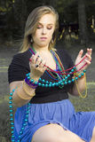 Eine Frau, die mehrfarbige Karnevalperlen anhält Stockbild