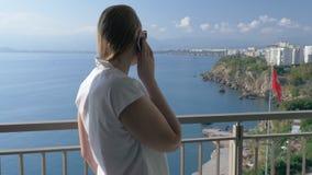 Eine Frau, die mit dem Telefon auf einem Hotelbalkon gegen die schöne Landschaft spricht stock video footage