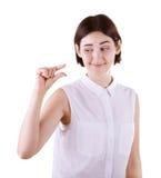 Eine Frau, die mit ihrer Hand etwas klein zeigt Ein skeptisches Mädchen lokalisiert auf einem weißen Hintergrund Eine sarkastisch Stockfotografie