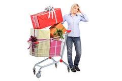Eine Frau, die nahe bei einem Einkaufswagen aufwirft Lizenzfreie Stockfotografie