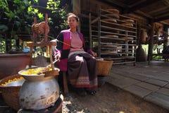 Eine Frau, die Seide von der Kokonseidenraupe zieht Lizenzfreies Stockbild