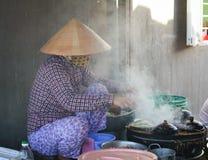Eine Frau, die traditionelle Kuchen in Phan Ri, Vietnam kocht Lizenzfreie Stockbilder