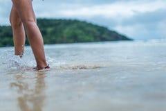 Eine Frau, die in die Untiefe auf dem Strand geht Lizenzfreie Stockfotos