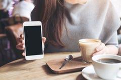 Eine Frau, die weißen Handy mit leerem schwarzem Tischplattenschirm mit Kaffeetassen auf Weinleseholztisch hält und zeigt Stockbild