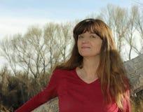 Eine Frau draußen gegen einen gefallenen Baum Stockfotos