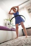 Eine Frau dreht ein hula Band zu Hause Selbsttraining mit einem Band lizenzfreie stockfotografie