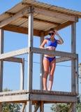 Eine Frau in einem blauen Badeanzug auf dem Wachturm von Rettern auf dem Strand stockfoto