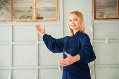 Eine Frau in einem blauen Kimono nimmt an chinesischer Kampfkunst Tai Chi-Nahaufnahme und Kopienraum teil lizenzfreie stockbilder