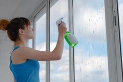 Eine Frau in einem blauen T-Shirt wäscht ein Fenster lizenzfreie stockbilder
