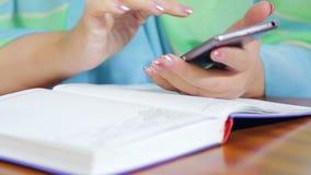 Eine Frau in einem Café arbeitet entfernt mit einem Telefon und einem Tagebuch stock video footage