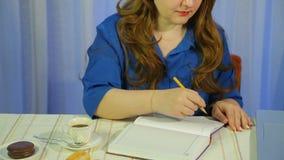 Eine Frau in einem Caf? an einem trinkenden Kaffee der Tabelle und Arbeiten in einem Tagebuch stock video