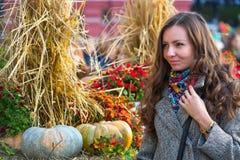 Eine Frau in einem grauen Mantel und in einem farbigen Schal im Herbst in Moskau stockbild
