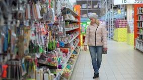 Eine Frau in einem Hut und in den Wegen einer unten Jacke durch den Supermarkt Sie betrachtet die Waren auf den Regalen, wählt a stock video footage