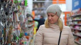 Eine Frau in einem Hut und in den Wegen einer unten Jacke durch den Supermarkt Sie betrachtet die Waren auf den Regalen, wählt a stock footage