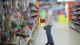 Eine Frau in einem Hut und in den Wegen einer unten Jacke durch den Supermarkt Sie nimmt die Waren vom Regal, wählt einen Kauf stock video footage