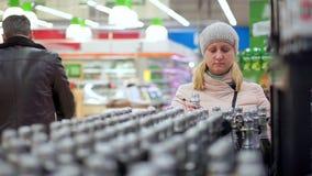 Eine Frau in einem Hut und in den Wegen einer unten Jacke durch den Supermarkt Sie wählt Champagner stock video footage