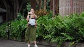 Eine Frau in einem Kleid mit einem Baby in einem Riemen geht entlang die Palmen und Trieb, die an einem Handy Video sind stock video footage