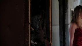 Eine Frau in einem langen Kleid kommt in den Raum stock video footage