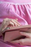Eine Frau in einem Nachthemd arbeitet mit einer Tablette beim Lügen im Bett Sie berührt den Schirm mit ihren Fingern Lizenzfreie Stockfotografie