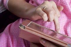 Eine Frau in einem Nachthemd arbeitet mit einer Tablette beim Lügen im Bett Sie berührt den Schirm mit ihren Fingern Lizenzfreies Stockbild