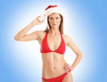 Eine Frau in einem roten Badeanzug und in einem Weihnachtshut Stockfotografie
