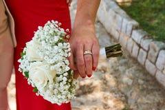 Eine Frau in einem roten Kleid, das Heiratsblumenstrauß hält stockbild