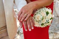 Eine Frau in einem roten Kleid, das Heiratsblumenstrauß hält lizenzfreies stockfoto