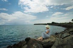 Eine Frau in einem Strohhut sitzt auf dem Strand des Meeres und untersucht heraus den Abstand auf dem Horizont stockfotos