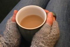 Eine Frau in einem cosy Pullover hält eine Tasse Tee oder Kaffee auf ihrem Schoss Lizenzfreies Stockbild