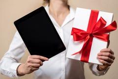 Eine Frau in einem weißen Hemd hält ein Geschenk, eine schwarze Tablette und weiße Geschenkbox Lizenzfreies Stockbild