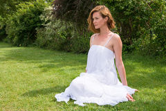 Eine Frau in einem weißen Kleid, das auf dem Gras und den Blicken in den Abstand sitzt Stockbilder