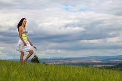 Eine Frau in einem weißen Rock geht über eine Wiese unter ein bewölktes s Stockfotos