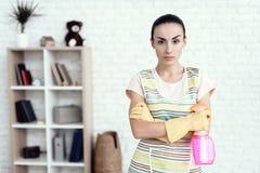 Eine Frau in einem weißen T-Shirt, das zu Hause mit Kapitalien für das Säubern des Hauses aufwirft Lizenzfreies Stockfoto