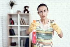 Eine Frau in einem weißen T-Shirt, das zu Hause mit Kapitalien für das Säubern des Hauses aufwirft Lizenzfreie Stockfotos