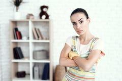 Eine Frau in einem weißen T-Shirt, das zu Hause mit Kapitalien für das Säubern des Hauses aufwirft Stockfotos