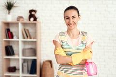 Eine Frau in einem weißen T-Shirt, das zu Hause mit Kapitalien für das Säubern des Hauses aufwirft lizenzfreies stockbild