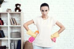 Eine Frau in einem weißen T-Shirt, das zu Hause mit Kapitalien für das Säubern des Hauses aufwirft Stockbilder