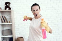 Eine Frau in einem weißen T-Shirt, das zu Hause mit Kapitalien für das Säubern des Hauses aufwirft Lizenzfreie Stockbilder