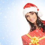 Eine Frau in einem Weihnachtshut, der ein Geschenk anhält Stockbilder