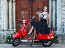 Eine Frau in einem Weinlesekleid, das auf einem Roller sitzt Lizenzfreies Stockbild