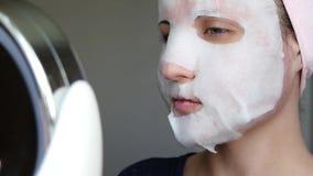 Eine Frau in einer kosmetischen Maske betrachtet im Spiegel Sch?nheitskonzept, Problemhaut, Antialtern Cosmetology stock video