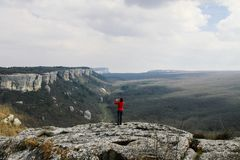Eine Frau in einer roten Strickjacke steht auf einen Berg und fotografiert eine Berglandschaft stockfoto