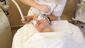 Eine Frau empf?ngt ein Verfahren des S?uberns und des Anhebens der Gesichtshaut im Badekurort stock video footage
