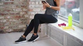 Eine Frau entspricht mit ihren Freunden an einem Handy nach körperlichem Training stock video