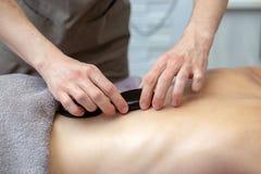 Eine Frau erh?lt eine Warmsteinmassage an einem Badekurort lizenzfreies stockbild
