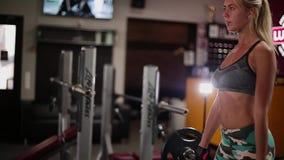 Eine Frau führt eine Übung mit einem Barbell in einem Fitness-Club durch stock footage
