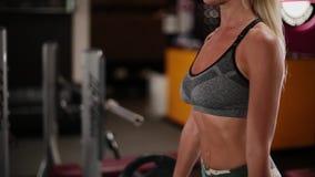 Eine Frau führt eine Übung mit einem Barbell in einem Fitness-Club durch stock video footage