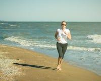 Eine Frau führt eine Übung auf dem Berg das Meer in den Strahlen der Sonne durch getont Lizenzfreie Stockfotografie